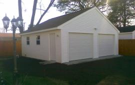 Garage with a roof and white vinyl siding and windows
